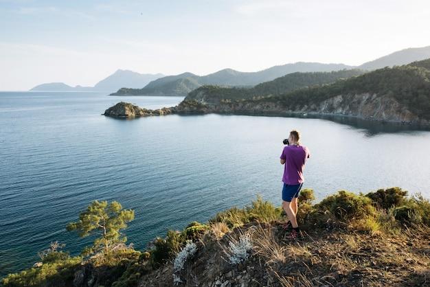 夕方にはトルコの海岸の青い地中海を眺める観光客