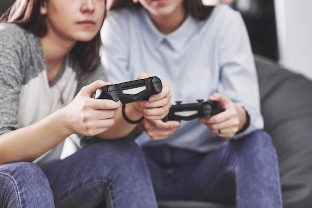 双子の姉妹姉妹がコンソールで遊ぶ。女の子はジョイスティックを手に持って楽しんでいます