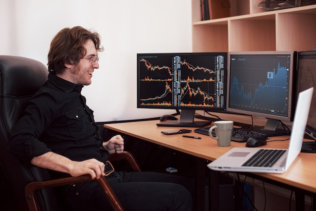 オンラインで株を取引するビジネスマン。株式ブローカーが複数のコンピューター画面でグラフ、インデックス、数値を確認します。ビジネスの成功の概念
