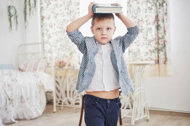 宿題をしている彼の頭の上の本で勤勉な少年の写真。男子生徒は宿題をするのにうんざりしている