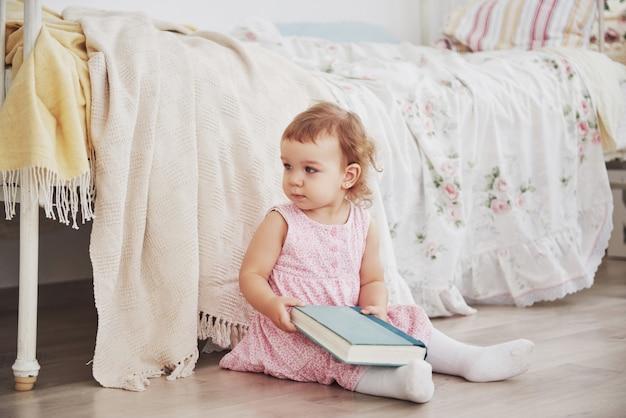 美しい小さな女の子がおもちゃを演奏します。青い目のブロンド。白い椅子。子供部屋。幸せな小さな少女の肖像画。幼年期のコンセプト