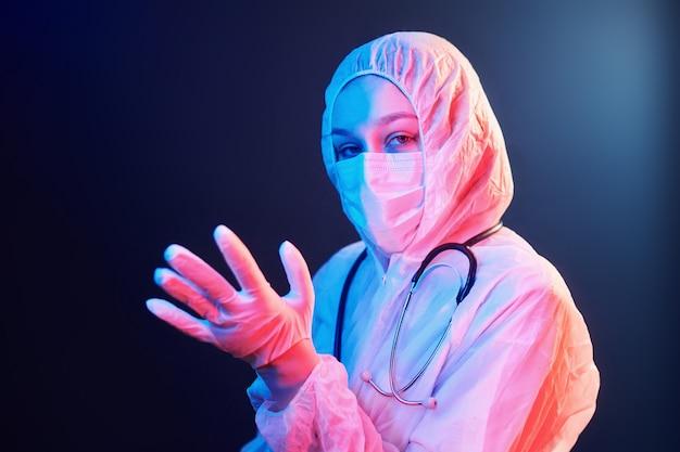Медсестра в маске и белой униформе стоит в комнате с неоновым освещением
