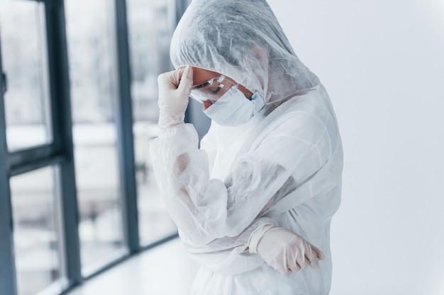 気分が悪く、疲れており、落ち込んでいる。白衣、防御的なアイウェア、マスクの女医科学者の肖像