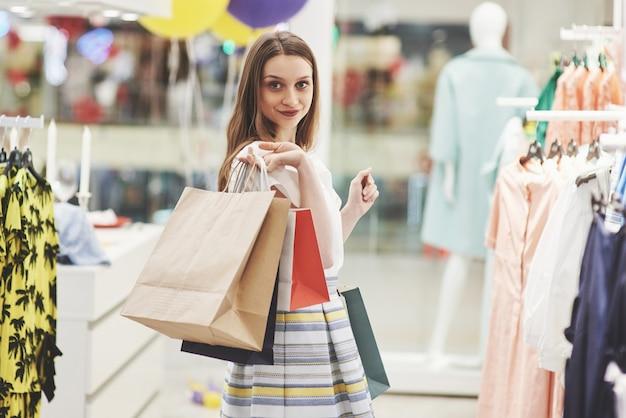 ショッピングの女性。ショッピングを楽しんで買い物袋を持つ幸せな女。消費主義、ショッピング、ライフスタイルのコンセプト