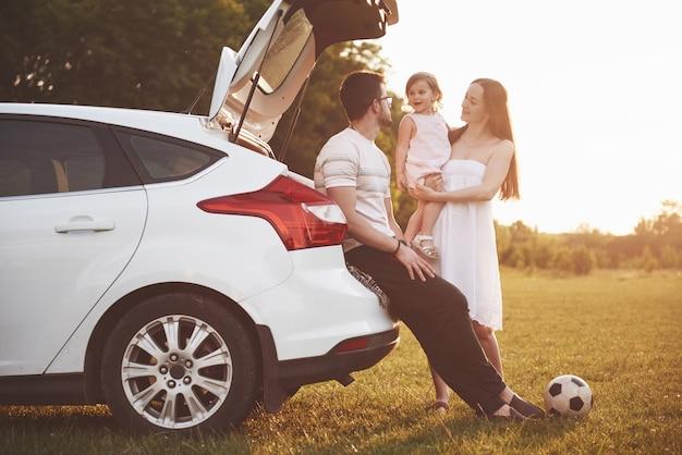 Довольно молодая семейная пара и их дочь отдыхают на природе.