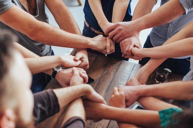 多様な手のグループが一緒に参加します。チームワークと友情