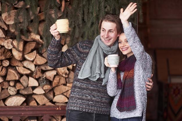 幸せな男と冬に屋外のカップを持つきれいな女性の写真。冬の休日と休暇。幸せな男と女のクリスマスカップルは、ホットコーヒーを飲みます。こんにちは隣人