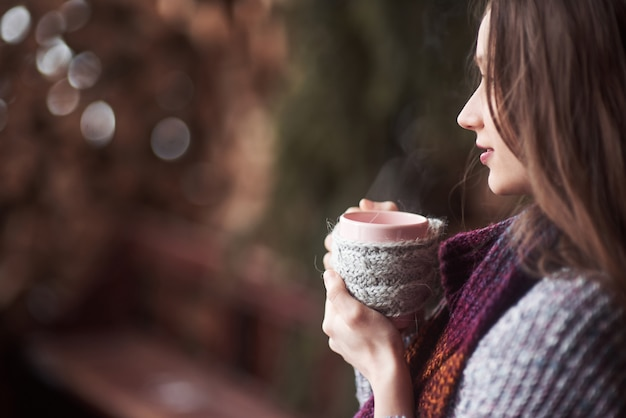 Оман в теплой вязаной одежде пьет чашку горячего чая или кофе на открытом воздухе