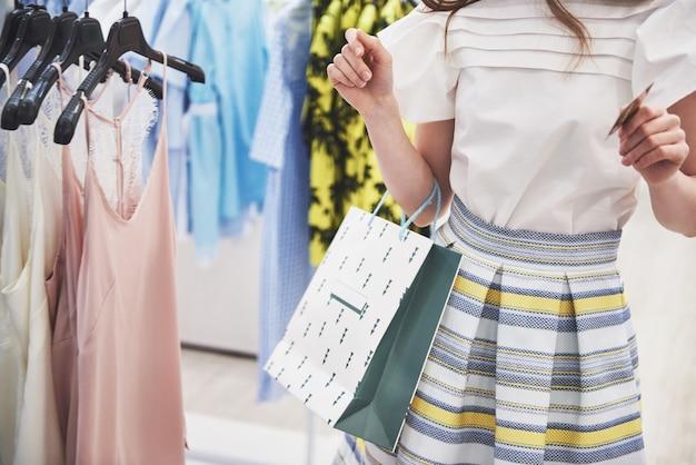 ショッピングの女性。ショッピングバッグや買い物で楽しんでいるクレジットカードで幸せな女。消費主義、ショッピング、ライフスタイルのコンセプト