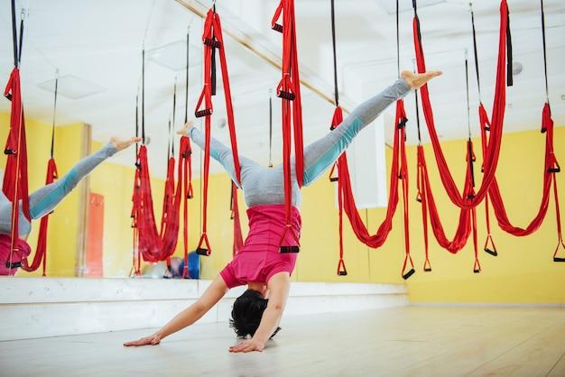 Молодая женщина делает упражнения йоги антигравитации