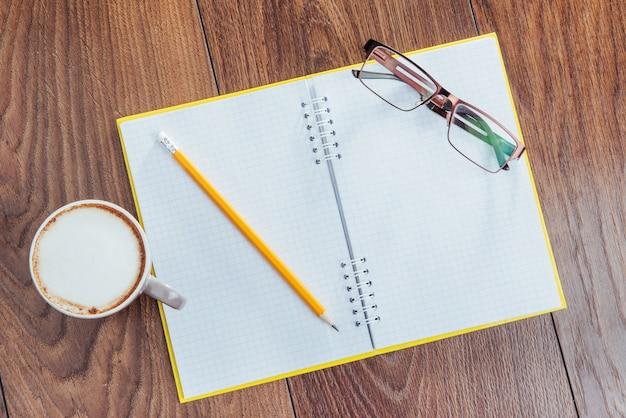 木製のノート鉛筆、コーヒー、花。