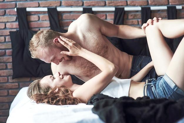 У привлекательных молодых любовников есть пары, играющие вместе в постели, в сексуальном белье в гостиничном номере.