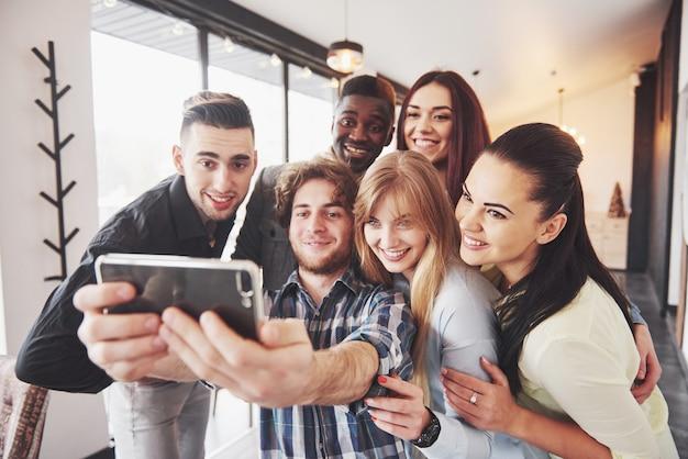 Автопортрет единства расы африканских, американских, азиатских, кавказских друзей, счастливых бородатых мужчин и красивых женщин в красной шляпе санты, показывающих большой палец вверх, вроде бы, нормально показывать камеру в офисе