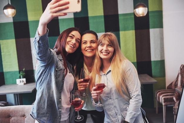 Картина представляет счастливую группу друзей с красным вином, принимая селфи
