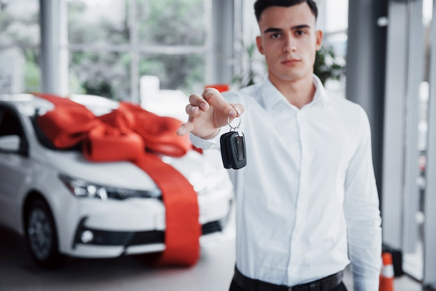 彼の手でキーを持つ若いビジネスマンは、キャビンで車を買います。