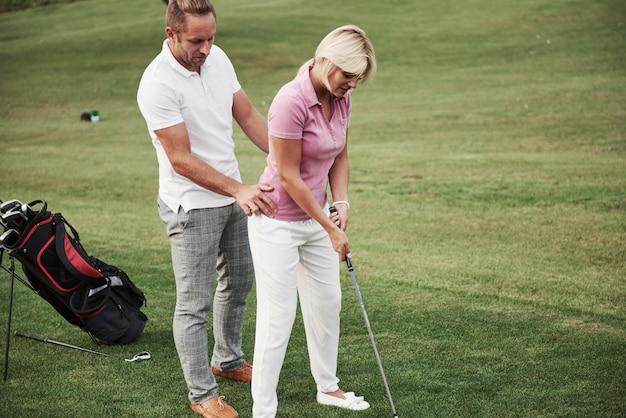 Девушка играя в гольф и ударяя короткой клюшкой на зеленом цвете. ее учитель помогает изучить технику и сделать ее первые удары