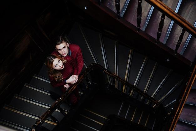 Пара молодых людей на деревянной лестнице