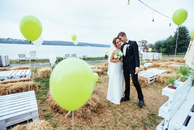 美しい若い結婚式のカップルがキス、花と金髪の花嫁
