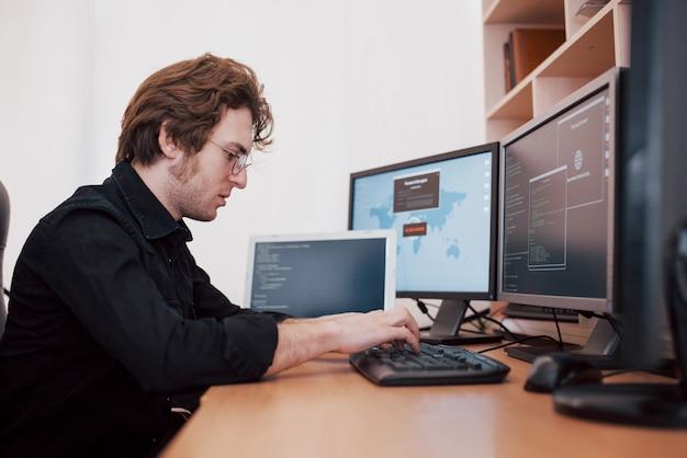 若い危険なハッカーは、機密データをダウンロードしてウイルスをアクティブにすることで、政府のサービスを破壊します。多くのモニターが搭載されたラップトップコンピューターを使用している男性