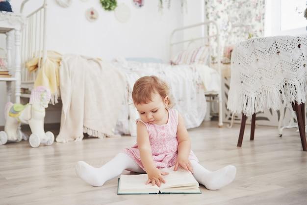おもちゃを遊んで美しい少女。青い目のブロンド。白い椅子。子供部屋。幸せな小さな少女の肖像画。子供の頃のコンセプト