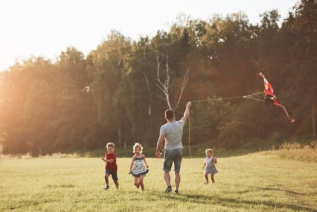 Счастливая семья отца и ребенка бегают с воздушным змеем на лугу