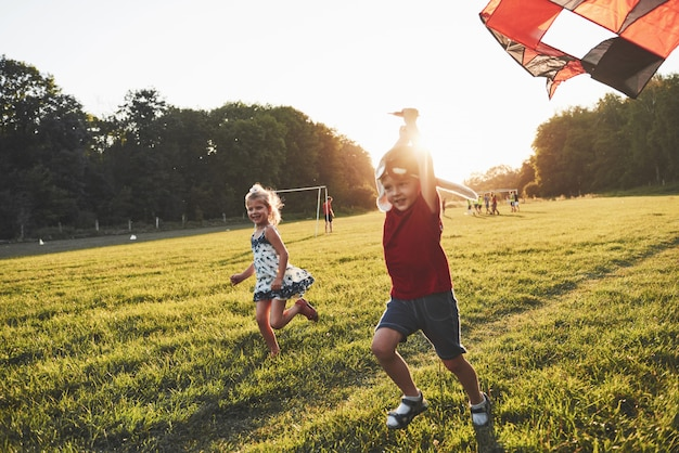 Счастливые дети запускают змея в поле на закате. маленький мальчик и девочка на летних каникулах