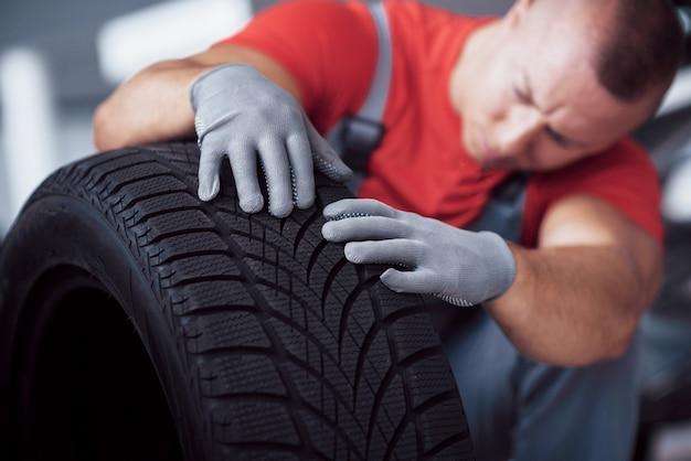 修理ガレージでタイヤタイヤを保持しているメカニック。冬用および夏用タイヤの交換