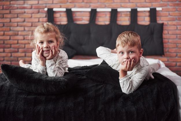 小さな子供、男の子と女の子を敷設し、毛布でベッドカバーの上に枕で遊んで