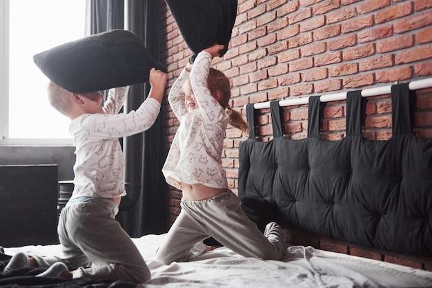 いたずらな子供たち男の子と女の子が寝室のベッドで枕投げをしました。彼らはその種のゲームが好きです