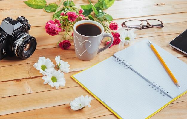 На деревянной тетради карандаш, кофе и цветы.