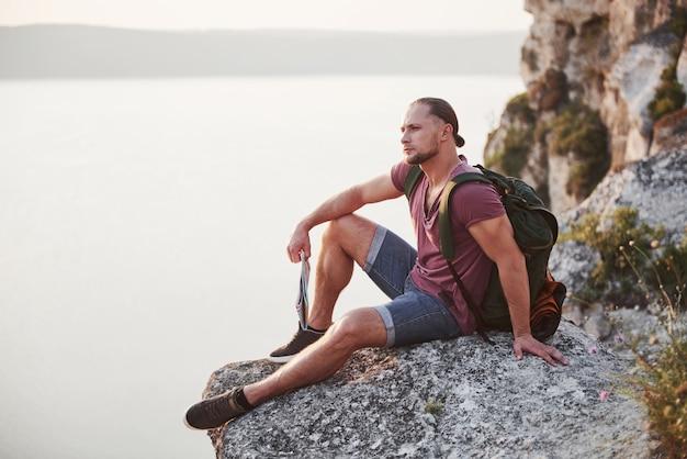 Успешный человек турист на вершине скалы с костра. путешествие по горам и побережью, свобода и концепция активного образа жизни