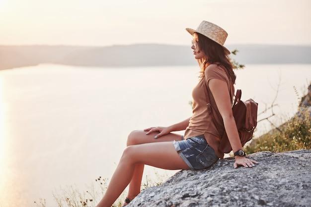 マウントの上と美しい湾の風景を見て若い観光客の女性。崖の上にリラックスできるバックパックでハイキングの女性