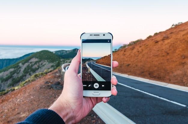 彼の携帯電話から道路の写真を撮る観光客