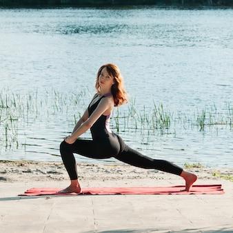 屋外できれいな女性の練習ヨガ運動に合う