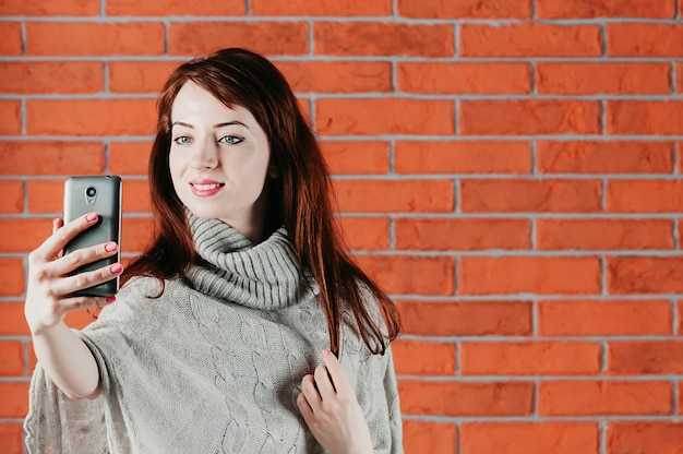 Красивая девушка делает селфи с смартфона, улыбаясь, одетый в серый пуловер