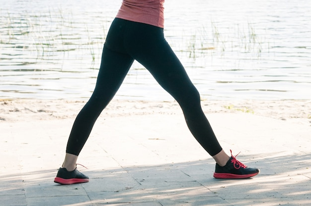 屋外の黒いレギンスで女性の脚にフィット