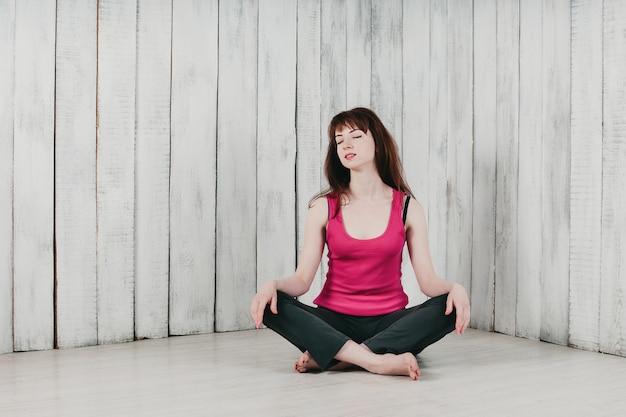 ピンクのトップの女の子、床にあぐらをかいて座って、笑みを浮かべて、明るい背景