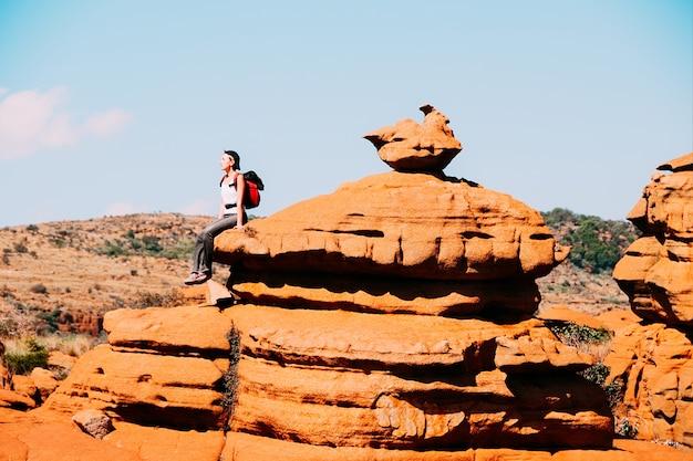 南アフリカのマガリスバーグ高原の岩の上に座っている旅行者
