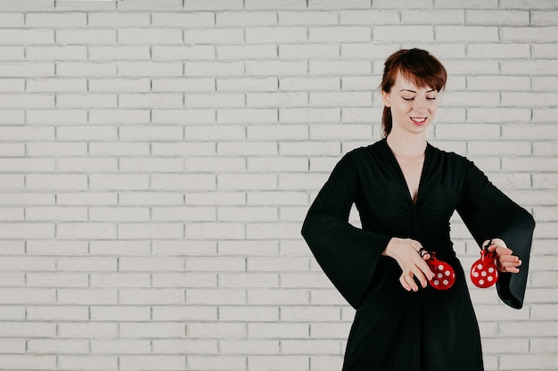 Молодая привлекательная женщина в черном платье, танцы с красными кастаньетами, улыбаясь, на белом фоне стены