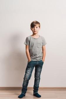 Милый мальчик у белой стены, серая рубашка, голубые джинсы
