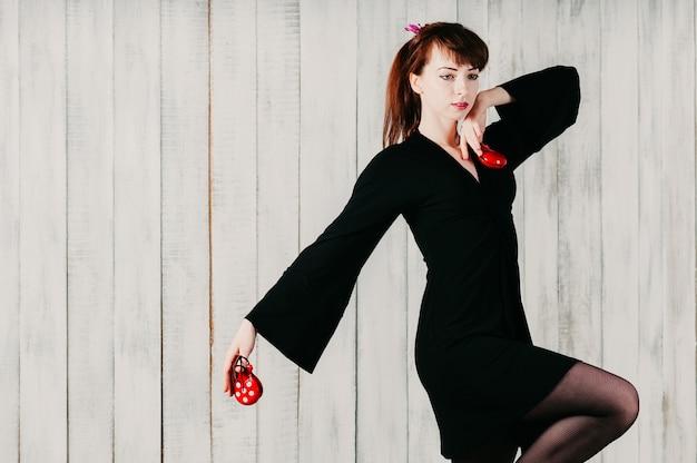 Молодая танцующая девушка в черном платье, с кастаньетами, светлый фон