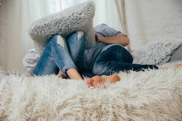 白いベッドの上のジーンズの若いカップル