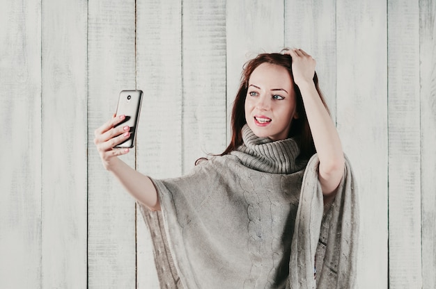Красивая девушка в сером пуловере, улыбаясь и делая селфи