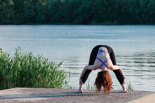 屋外できれいな女性のヨガの練習に合う