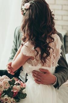 結婚式の花の花束、ベッドの上に座っているカップル、背面図