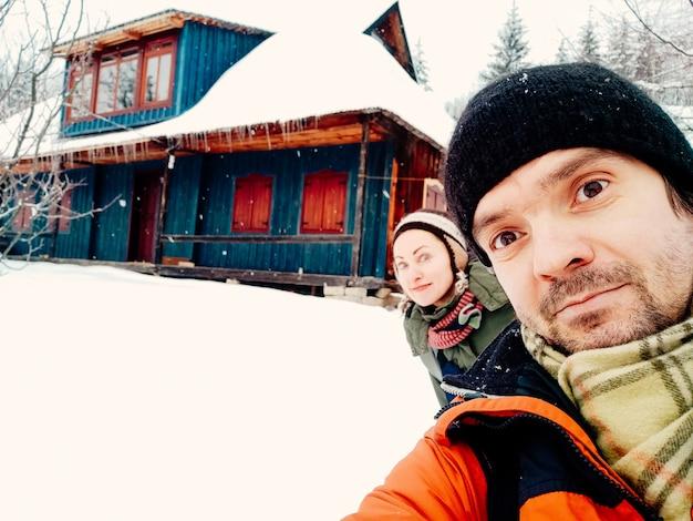 Улыбающаяся молодая пара весело на открытом воздухе зимой