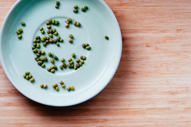 Плоские зеленые сухие бобы мунг, разбросанные на фоне блюдца, вид сверху