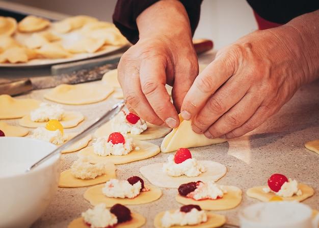 Руки готовят сыр и вишневые клецки