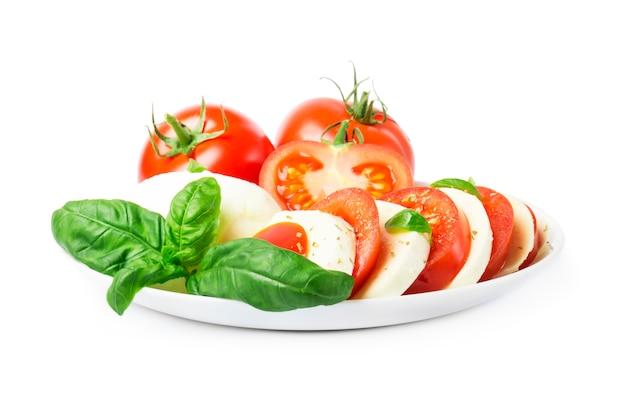 Салат капрезе со спелыми помидорами и сыром моцарелла со свежими листьями базилика.