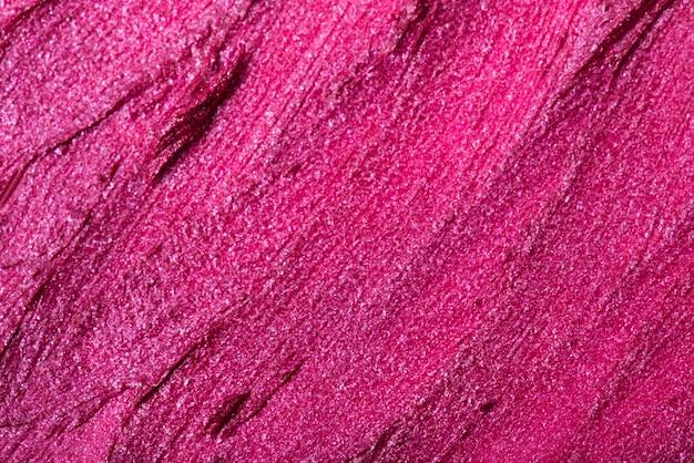 ピンクの口紅の質感のクローズアップ。背景として使用できます。
